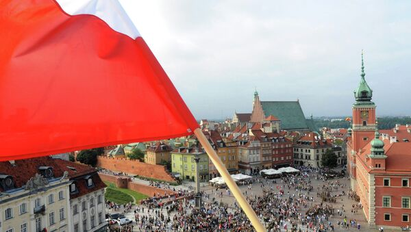 A Polish national flag waves above the Zamkowy Square as people stop to commemorate the 70th anniversary of the 1944 Warsaw Uprising, in Warsaw, Poland, Friday, Aug. 1, 2014 - Sputnik International