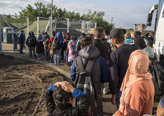 Migrants stand in line to get inside a new a reception camp near the village of Roszke, Hungary September 6, 2015