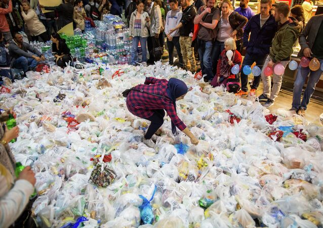 People surround hundreds of bags containing food as they wait for the arrival of a special train from Austria transporting hundreds of migrants at the main train station in Frankfurt am Main, western Germany, on September 5, 2015