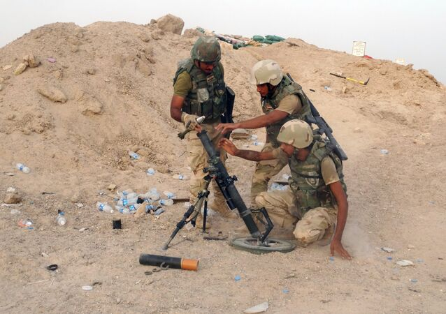 In this Thursday, Aug. 6, 2015 photo, Iraqi Army soldiers prepare to bomb Islamic State group positions at the front line in the eastern suburbs of Ramadi, Anbar province, Iraq