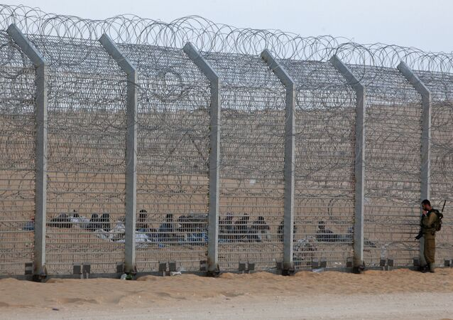 An Israeli soldier stands near the border fence between Israel and Egypt as African would-be immigrants sit on the other side near the Israeli village of Be'er Milcha, in this September 6, 2012 file photo
