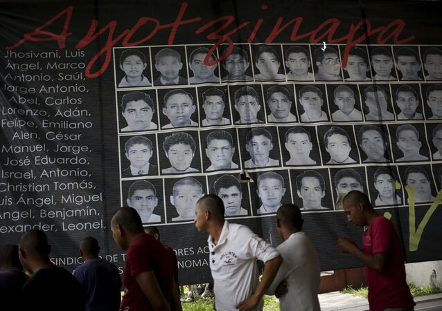 Newly enrolled students stand near a banner showing the photographs of the 43 missing students of the Ayotzinapa teachers' training college, at the college in Tixtla, on the outskirts oft Chilpancingo, in the Mexican state of Guerrero, August 16, 2015