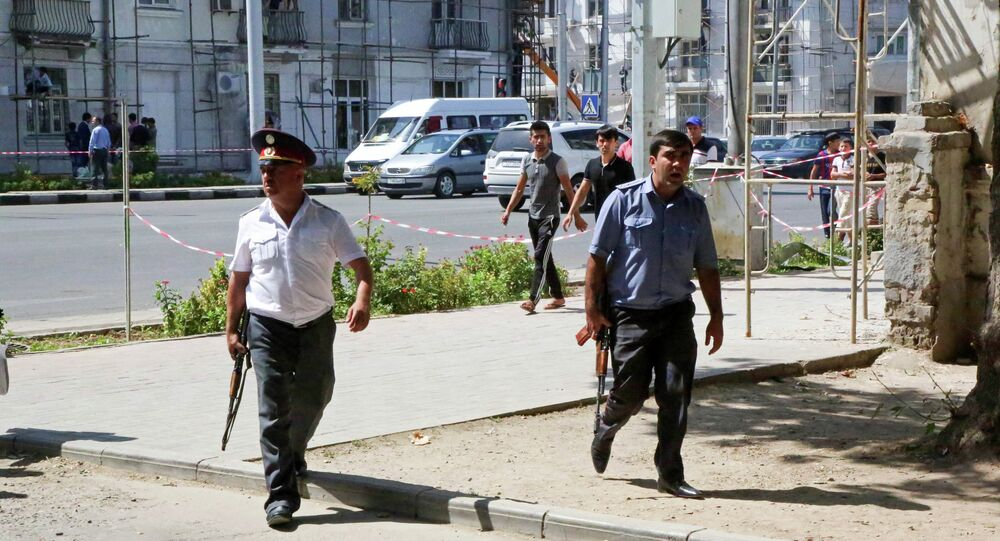 Police officers secure an area in the capital of Tajikistan, Dushanbe, where several Interior Ministry special forces officers and a traffic policeman were shot dead earlier on Friday, September 4, 2015.