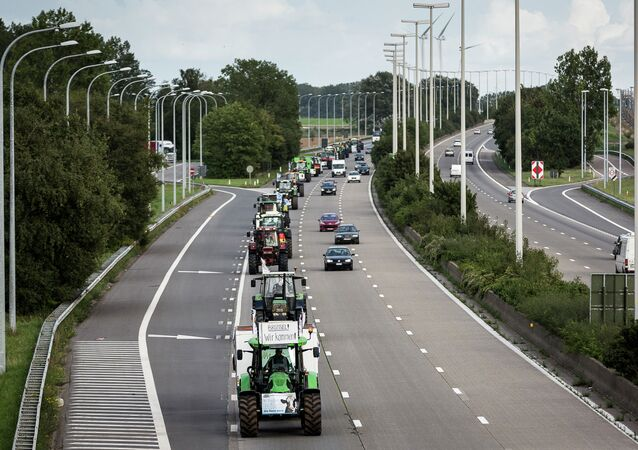 Farmers drive their tractors in a line down a main motorway outside of Brussels, Belgium on Sunday, Sept. 6, 2015. Farmers are expected to demonstrate in Brussels on Monday, Sept. 7, 2015