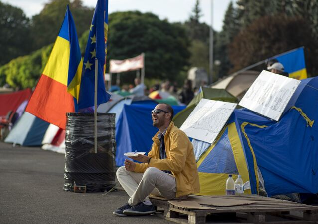 A demonstrator has breakfast as he sits next to tents set up by protesters in central Chisinau on September 7, 2015 after an anti-government rally.