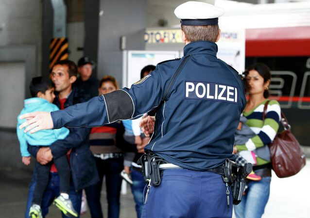 A police officer points the way as migrants arrive by train at the main railway station in Munich, Germany September 7, 2015