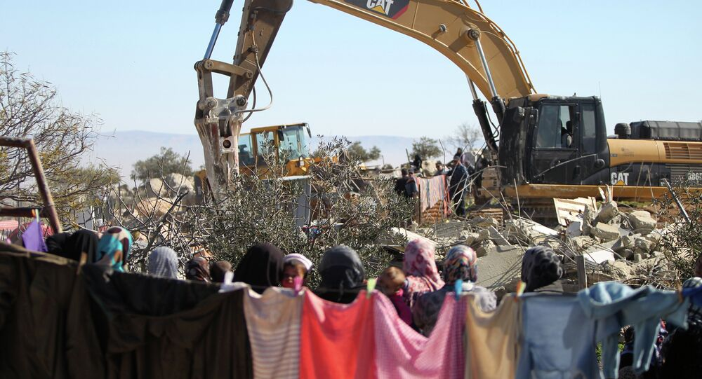 Palestinian women watches on as an Israeli army bulldozer with a demolition permit pulls down the house of the Palestinian Raba'ai family which Israeli authorities said was build without a permit, in Al-Dirat south of Yatta village near the West Bank town of Hebron on January 20, 2015.