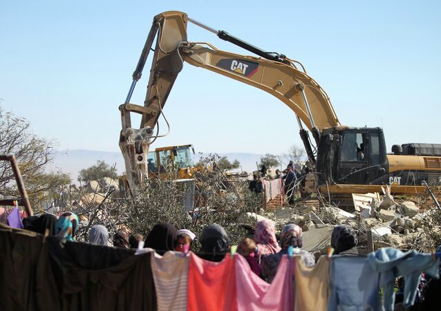 Palestinian women watch on as an Israeli army bulldozer with a demolition permit pulls down a house in the West Bank.