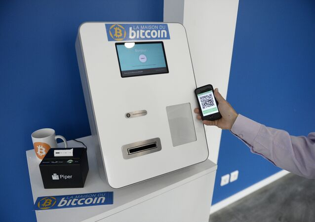 This picture taken on June 20, 2014, shows a man placing his phone next to a Bitcoins (virtual currency) dispenser at La Maison du Bitcoin in Paris.