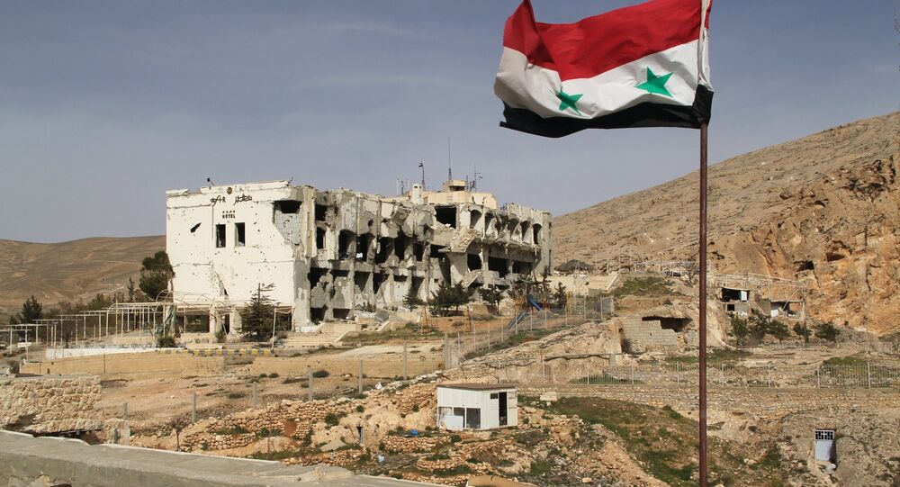 A Syrian flag on the background of ruined houses in the Syrian town of Maaloula, 55 km from Damascus, which was twice captured and looted by al-Nusra Front militants.