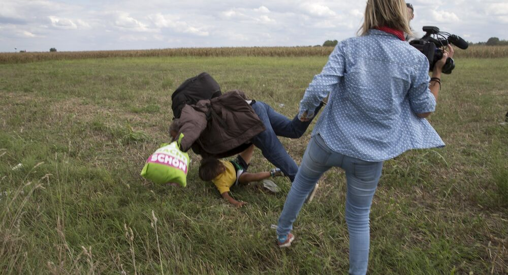 A refugee carrying a child falls after being tripped by a TV camerawoman while trying to escape from a collection point in Roszke village, Hungary.