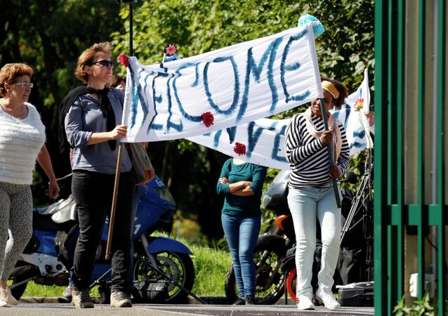 Neighbours hold a banner to cheer a group of migrants.