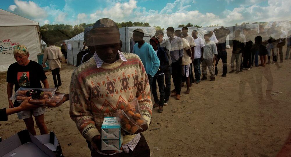 In this Tuesday, Aug. 4, 2015 file photo, migrants receive their food rations distributed by the Banque Alimentaire of Calais at a camp set in northern France.