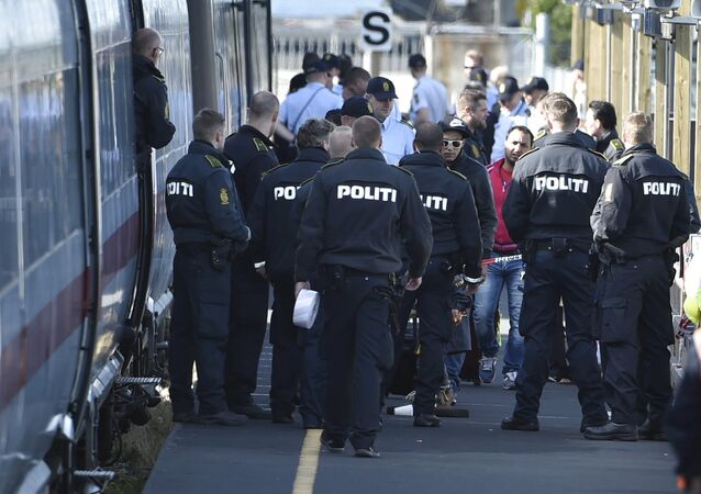 Danish police guard a train carrying migrants, mainly from Syria and Iraq, at Rodby train station, south of Denmark, September 9, 2015. The migrants, hoping to get to Sweden, arrived at Rodby on Tuesday night and refused to leave the train to get registered in Denmark.