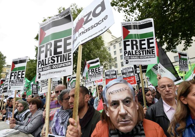 A demonstrator wears a Benjamin Netanyahu mask with a message written on it during a protest outside Downing Street in London, Britain September 9, 2015