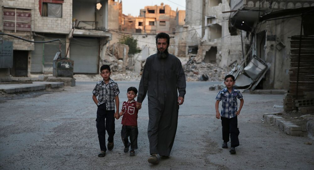 A Syrian man heads to a mosque with children in the rebel-held area of Douma, east of the capital Damascus