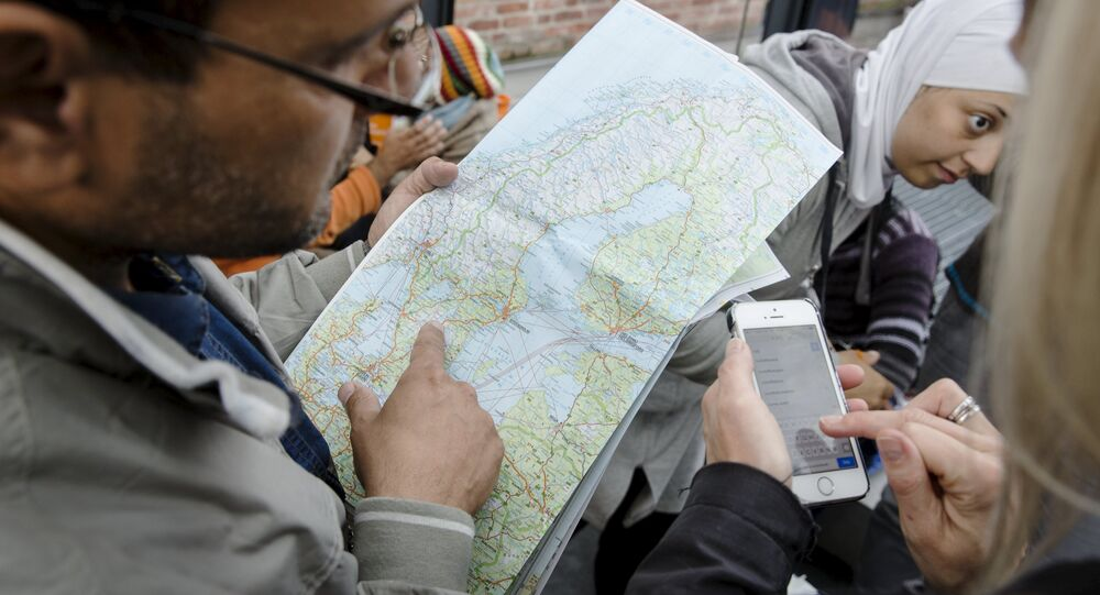 A migrant checks a map of Sweden after arriving at Malmo train station in Sweden September 10, 2015.