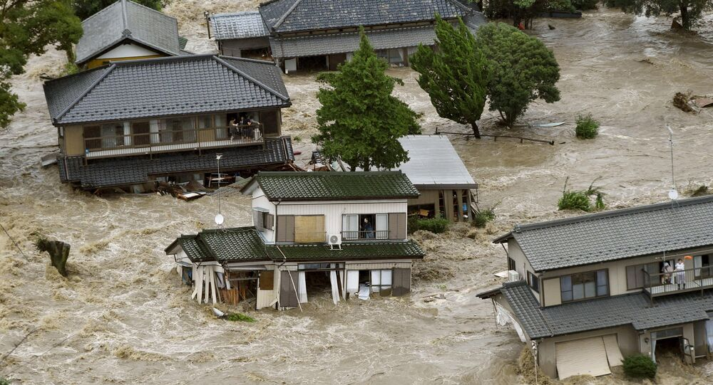 People wait to be rescued as floodwaters caused by Typhoon Etau engulf their homes.