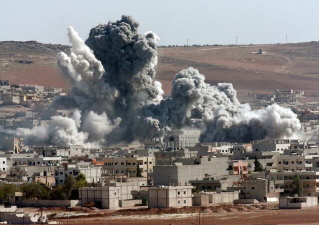 In this Oct. 22, 2014, file photo, thick smoke from an airstrike by the US-led coalition rises in Kobani, Syria, as seen from a hilltop on the outskirts of Suruc, at the Turkey-Syria border