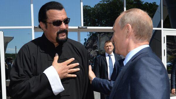 Russian President Vladimir Putin (R) speaks with US action movie actor Steven Seagal (L) at the Russia's first ever Eastern Economic Forum (EEF) in Vladivostok on September 4, 2015 - Sputnik International