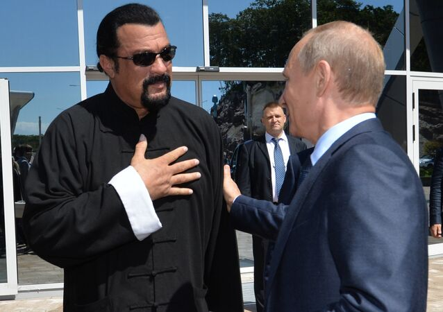 Russian President Vladimir Putin (R) speaks with US action movie actor Steven Seagal (L) at the Russia's first ever Eastern Economic Forum (EEF) in Vladivostok on September 4, 2015