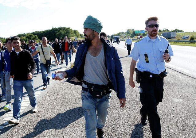 Migrants walk north on the highway in Southern Denmark, Wednesday, Sept. 9, 2015