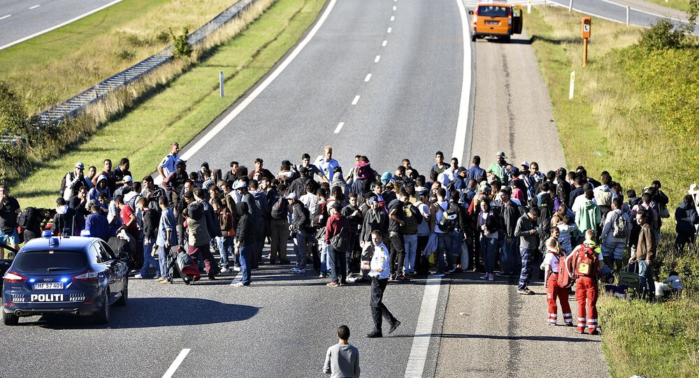 A group of refugees and migrants who were walking north stand on the highway in southern Denmark on Wednesday, Sept. 9, 2015