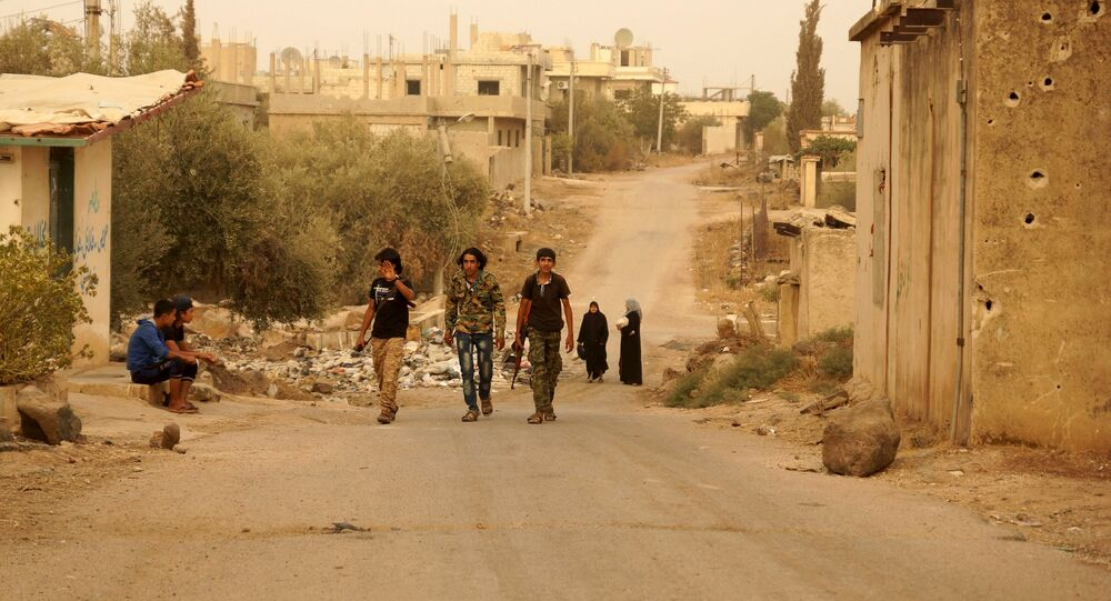 Free Syrian Army fighters walk with their weapons in the Deraa countryside September 9, 2015