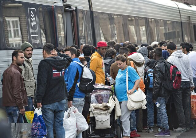 Migrants, mainly from Syria, prepare to board a train headed for Sweden, at Padborg station in southern Denmark, 10 September 2015