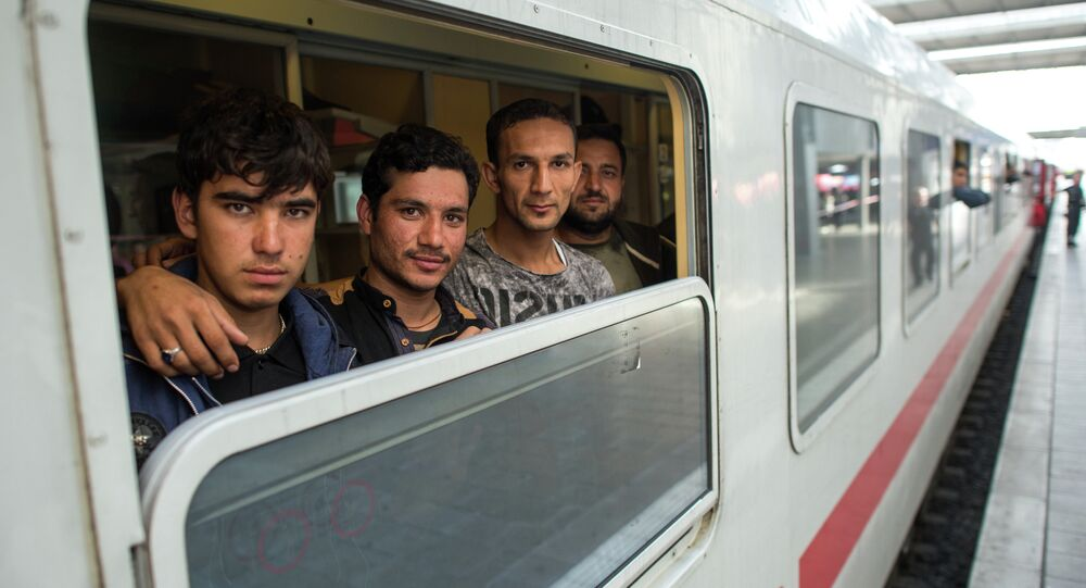 Friends Ibrahim, Hamayoun and Nomi, from left, refugees from Afghanistan, travel in a special train to Dortmund, photographed at the central train station in Munich, Germany, Friday Sept. 11, 2015.