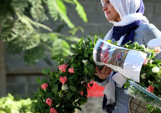 Libyan woman carries a wreath with a photo of U.S. Ambassador Chris Stevens on it as she and others gather to pay their respect to the victims of the Tuesday, Sept. 11, 2012 attack on the U.S. consulate, in Benghazi, Libya, Monday, Sept. 17, 2012