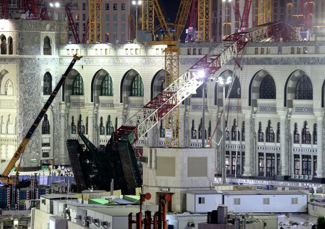 A towering construction crane, center, is seen collapsed over the Grand Mosque, in Mecca, Saudi Arabia, early Saturday morning, Sept. 12, 2015