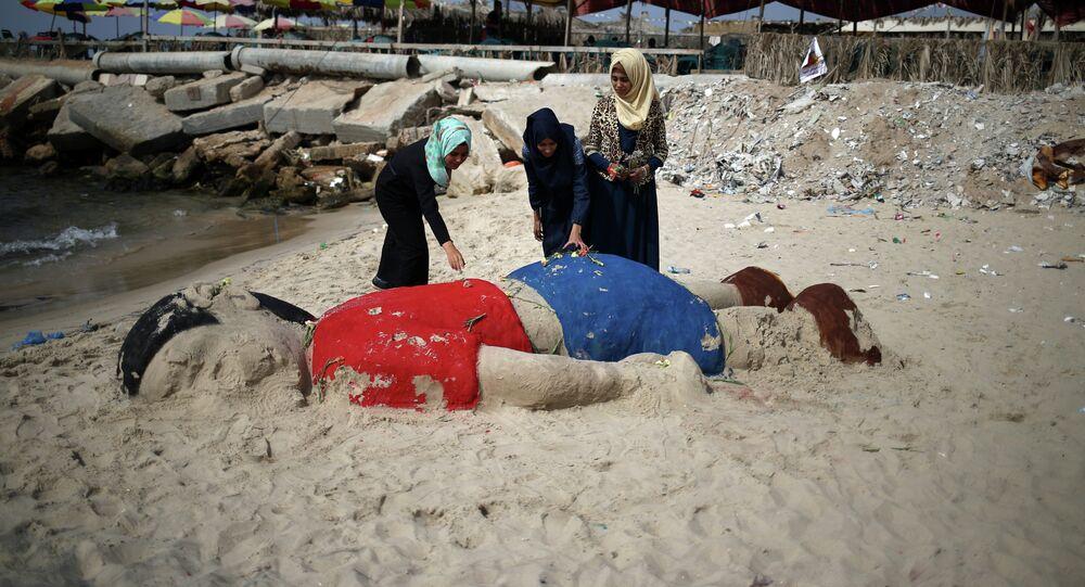 Palestinian girls put flowers on a sand sculpture by Indian artist Sudarsan Pattnaik depicting Syrian boy Aylan Kurdi, a three-year-old boy who drowned off Turkey, on September 7, 2015, on Gaza city beach