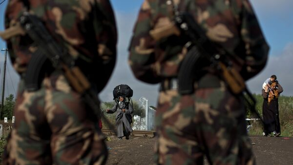 Hungarian army officers stand at the Serbian-Hungarian border as a Syrian refugee women crosses, near Roszke, southern Hungary, Saturday, Sept. 12, 2015 - Sputnik International