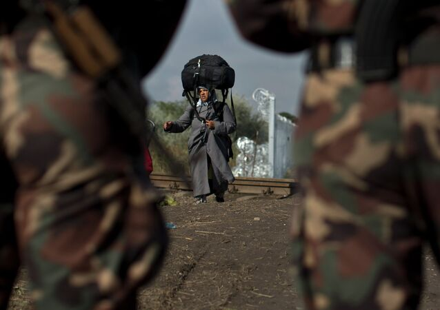 Hungarian army officers stand at the Serbian-Hungarian border as a Syrian refugee women crosses, near Roszke, southern Hungary, Saturday, September 12, 2015