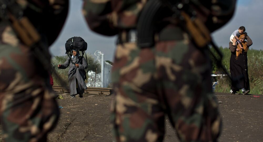 (File) Hungarian army officers stand at the Serbian-Hungarian border as a Syrian refugee women crosses, near Roszke, southern Hungary, Saturday, Sept. 12, 2015