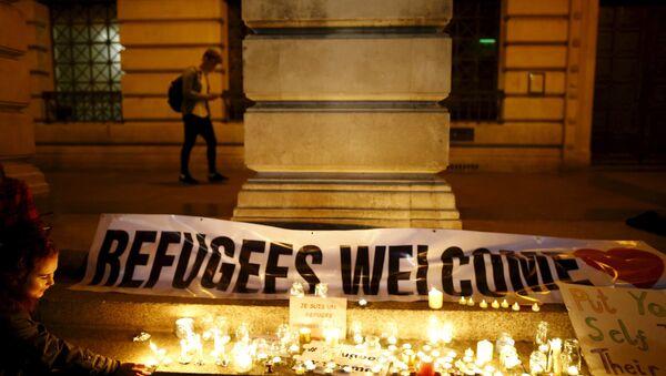 A woman lights a candle during a vigil for refugees in Nottingham, Britain, September 7, 2015 - Sputnik International