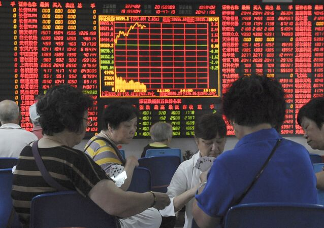 Investors play cards in front of an electronic board showing stock information at a brokerage house in Shanghai, China, September 9, 2015
