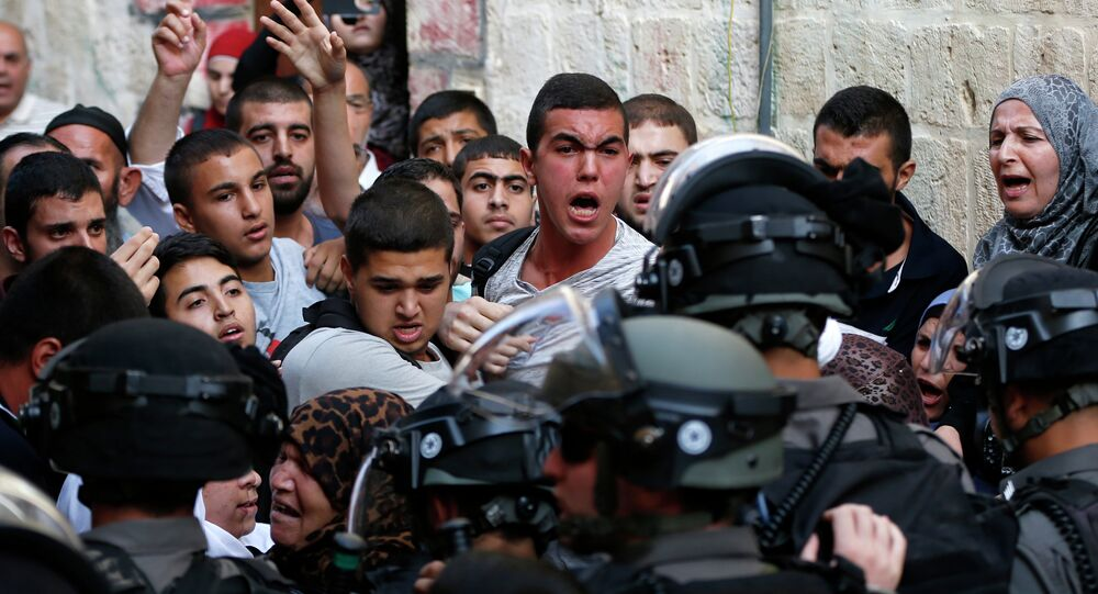 Palestinians shout in front of Israeli security forces who block a road leading to the Al-Aqsa mosque compound in Jerusalem's Old City on September 13, 2015