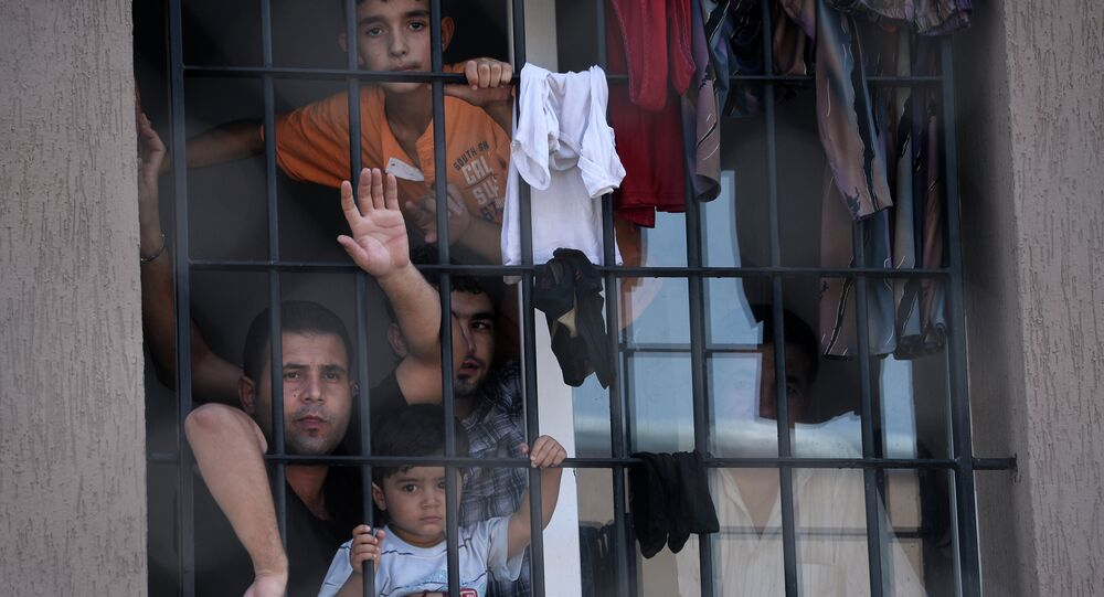 Refugees behind a barred window at Bulgaria's shelter for clandestine migrants near Lyubimets, as the small EU state finds it hard to cope with an ever rising number of Syrians fleeing conflict at home