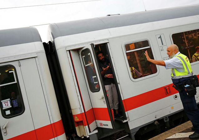 A security official of German rail operator Deutsche Bahn (DB) prevents migrants to disembark from their train at the main railway station in Frankfurt, Germany, September 13, 2015