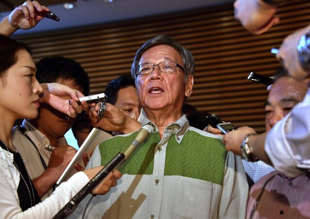 Okinawa Gov. Takeshi Onaga, center, speaks to the media after meeting with Japanese Prime Minister Shinzo Abe at Abe's office in Tokyo Friday, Aug. 7, 2015