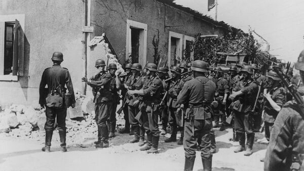 Storm troopers follow up the retreating enemy. The unit leader gives his men directions at a street crossing in Aisne, France on August 20, 1940 - Sputnik International