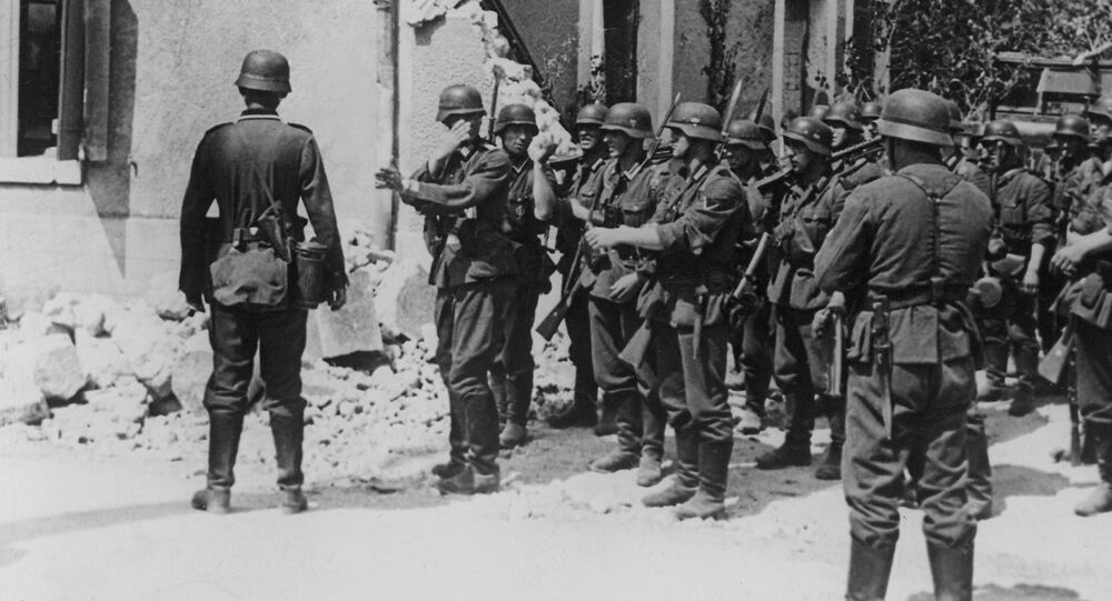 Storm troopers follow up the retreating enemy. The unit leader gives his men directions at a street crossing in Aisne, France on August 20, 1940