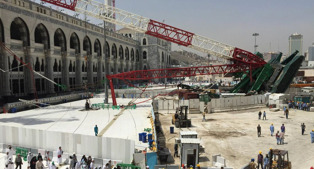 Muslim pilgrims walk near a construction crane which crashed in the Grand Mosque in the Muslim holy city of Mecca, Saudi Arabia September 12, 2015