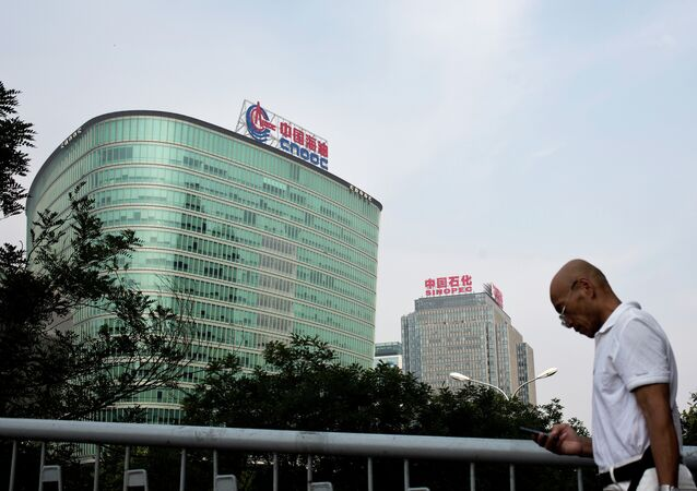 A man checks his mobile phone as he walks by buildings of China's state-owned companies, China National Offshore Oil Corp. (CNOOC), left, and China Petroleum & Chemical Corp. (Sinopec), in Beijing Monday, Sept. 14, 2015