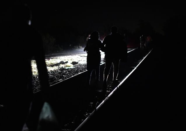 Syrian refugees and migrants cross the Serbian-Hungarian border as they walk on a railway line on September 1, 2015