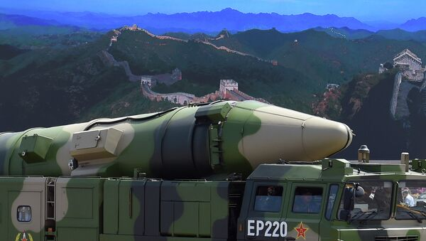 A military vehicle carries DF-21D missile past a display screen featuring an image of the Great Wall of China at Tiananmen Square in Beijing on September 3, 2015 - Sputnik International