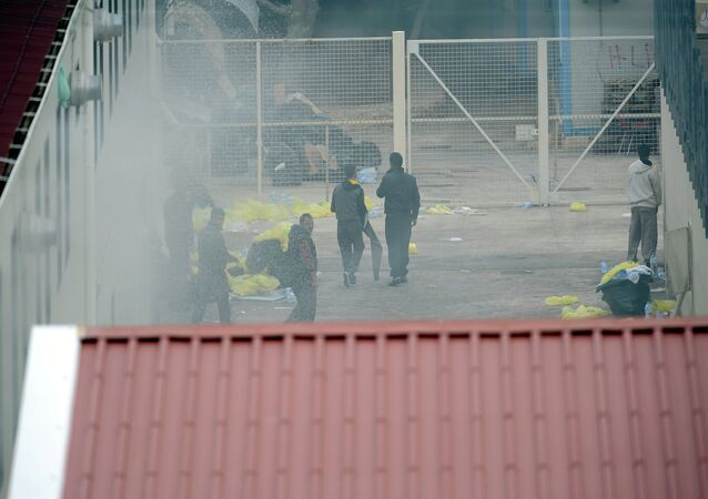 Migrants escape from smoke after a temporary detention center was set on fire, on the Italian island of Lampedusa, on April 11, 2011