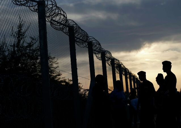 Hungarian policemen guard the fence on the border with Serbia near the Hungarian migrant collection point in Roszke, Hungary, September 14, 2015
